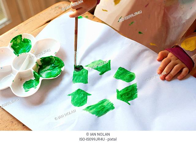 Child painting green recycling symbol