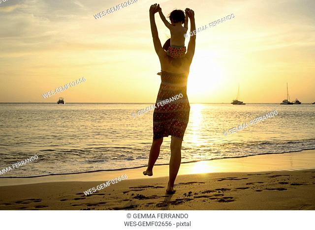 Thailand, Koh Lanta, back view of mother with baby girl on her shoulders at seashore during sunset