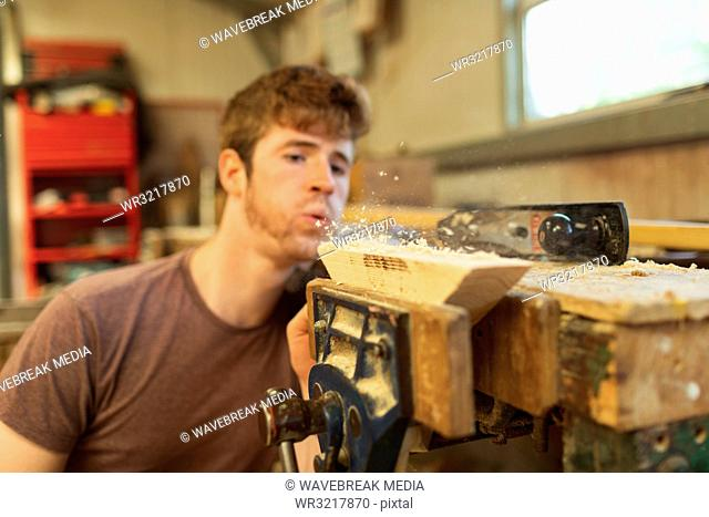 Male carpenter blowing wood shavings in workshop