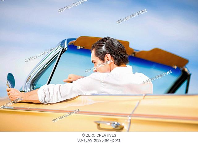 Young man driving convertible