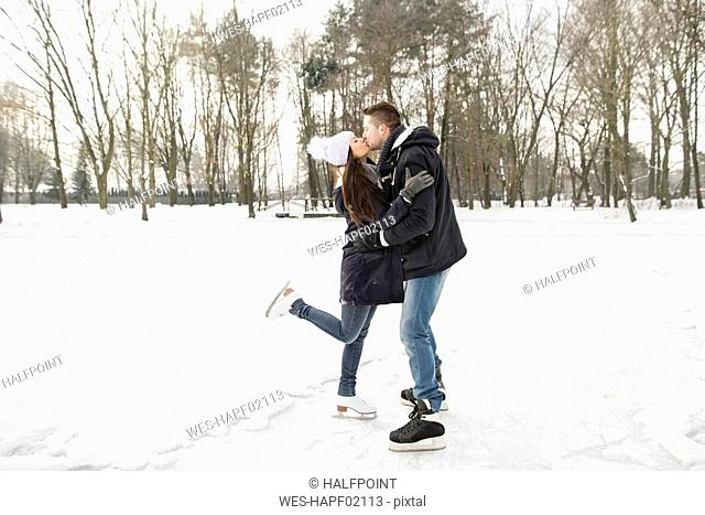 Couple ice skating on a frozen lake, kissing and embracing