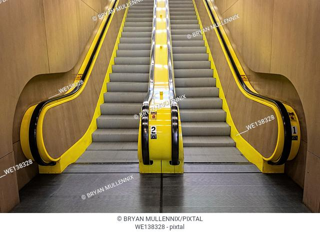 An empty yellow escalator leads up in building