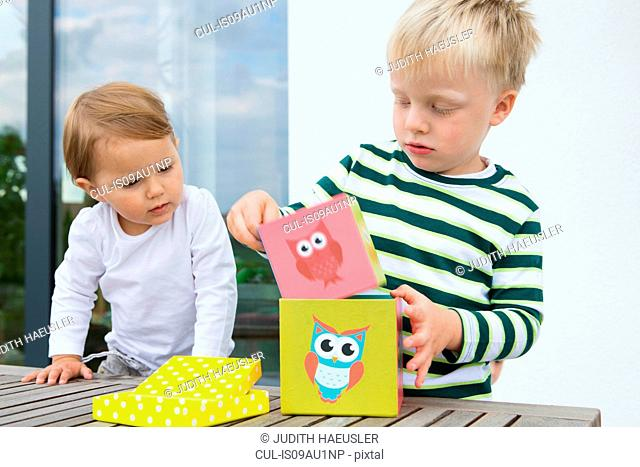 Boy and female toddler playing with building blocks on patio