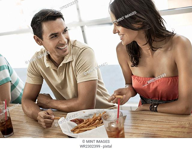 A young couple sitting together sharing a bowl of french fries in a diner