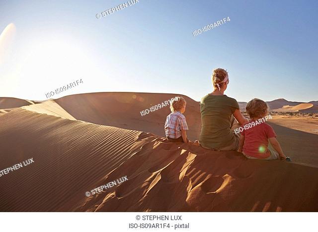 Mother and sons sitting on sand dune, Namib Naukluft National Park, Namib Desert, Sossusvlei, Dead Vlei, Africa