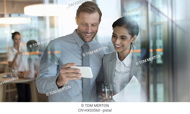Smiling businessman and businesswoman watching video on smart phone in office