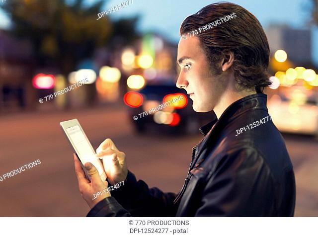 A young man uses a tablet along a street at dusk with the glowing screen illuminating his face; Edmonton, Alberta, Canada