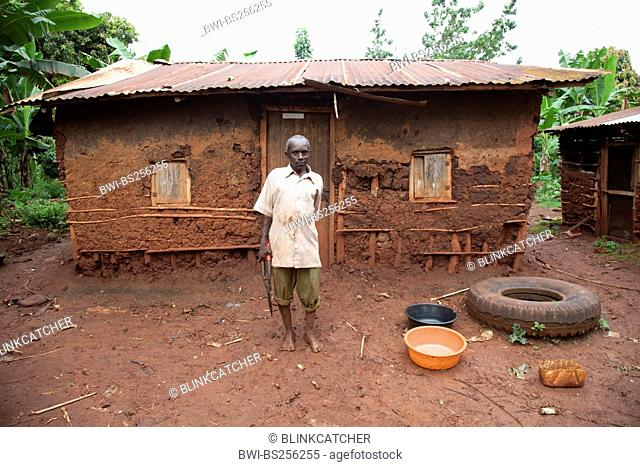 elderly man is standing on front of his simple mud house with a corrugated iron roof, Uganda, Jinja