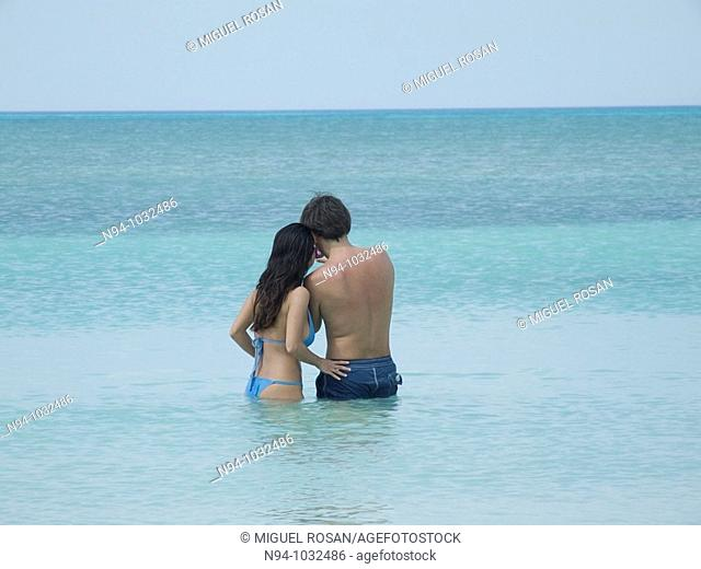 Young couple embracing in water on a Caribbean beach