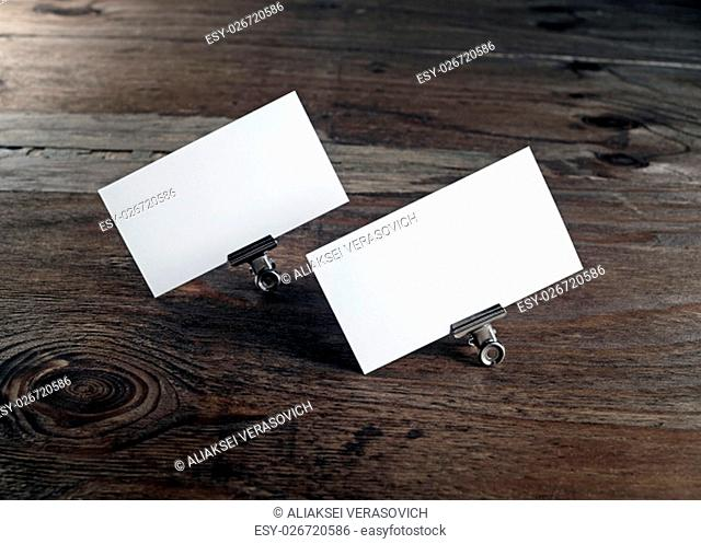 Two blank business cards in paper clips on dark wooden background. Blank template for ID. Mock-up for design presentations and portfolios