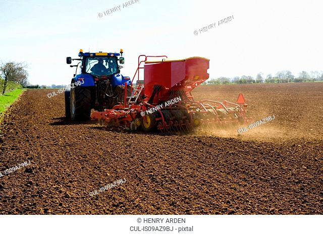 Farm tractor and seed drill sowing ploughed field in spring