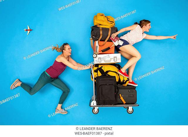 Friends pushing luggage trolley, hurrying for departure
