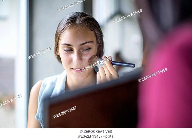 Girl applying make up while mother holding mirror
