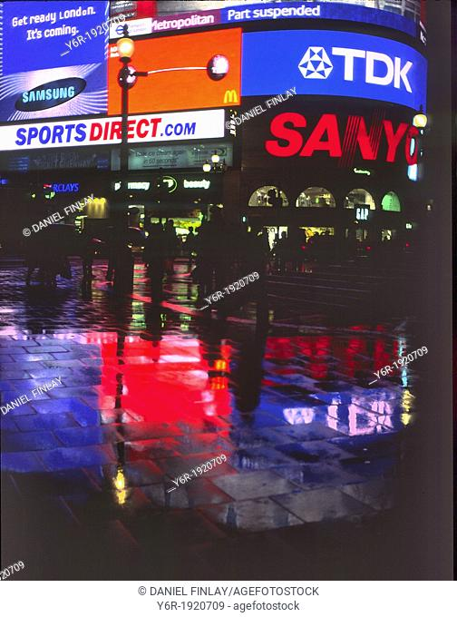 Reflections in rain after dark at Piccadilly Circus in the heart of London, England with the famous illuminated advertizing hoardings in the background