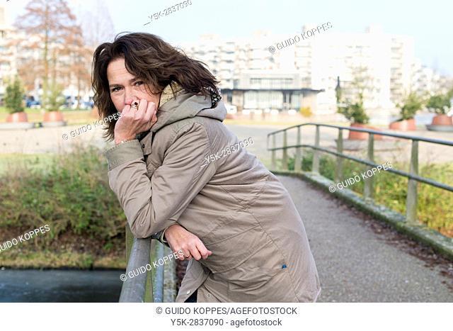 Zoetermeer, Netherlands. Portraitof a mid adult caucasian woman leaning over a bridge railing