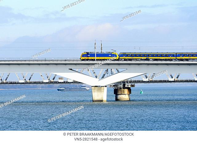 "MOERDIJK, THE NETHERLANDS â. "" JANUARY 29: Train rides on the railway bridge over the Hollands Diep in Holland on January 29, 2017"