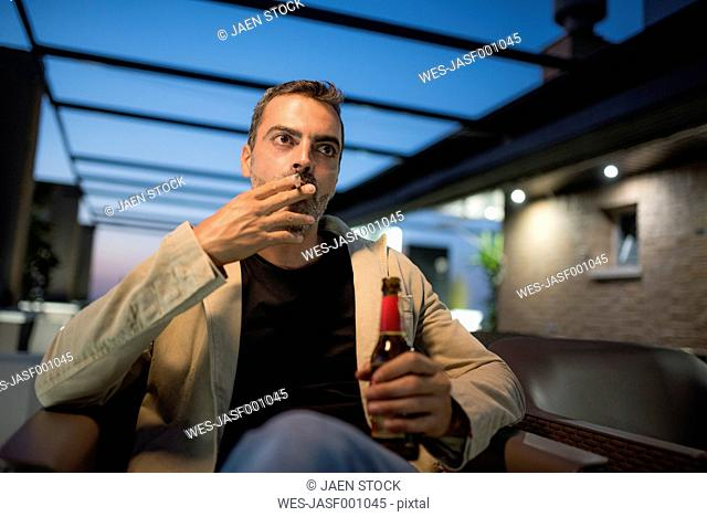 Smoking man with beer bottle sitting on roof terrace in the evening