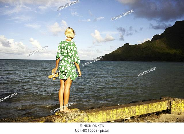 Young woman looking out over water