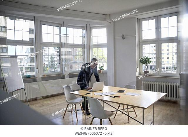 Mature businessman using laptop on boardroom table