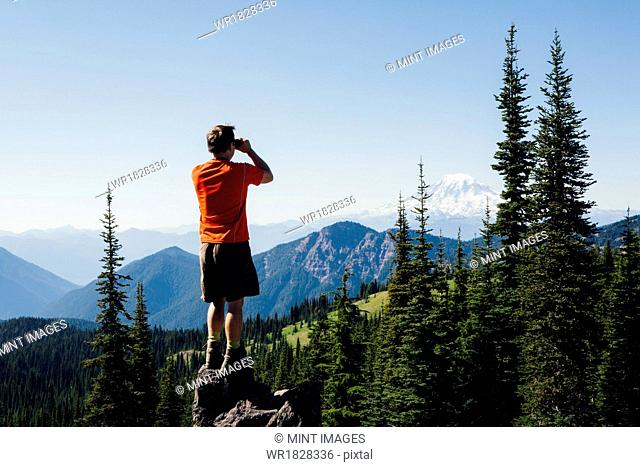 A man standing on a mountain ridge, taking a photograph of the landscape