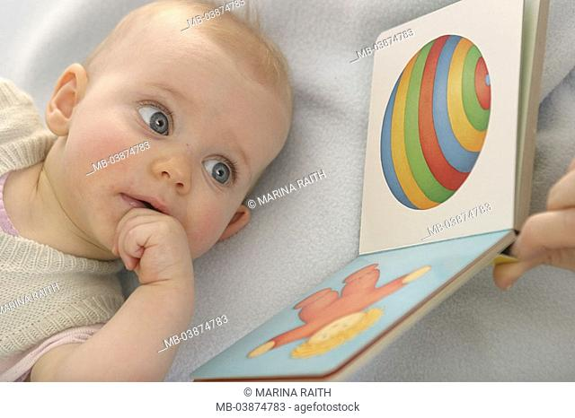 Toddler, lies, picture-book, looks at, portrait, broached, series, people, woman, mother, hand, detail, fingers, baby, 5 months, child, book, pictures