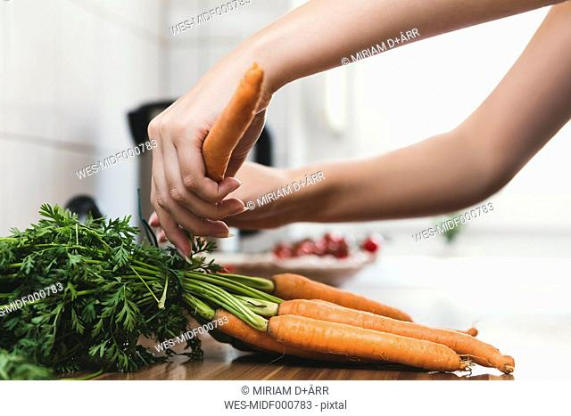Woman removing leaves from bunch of carrots