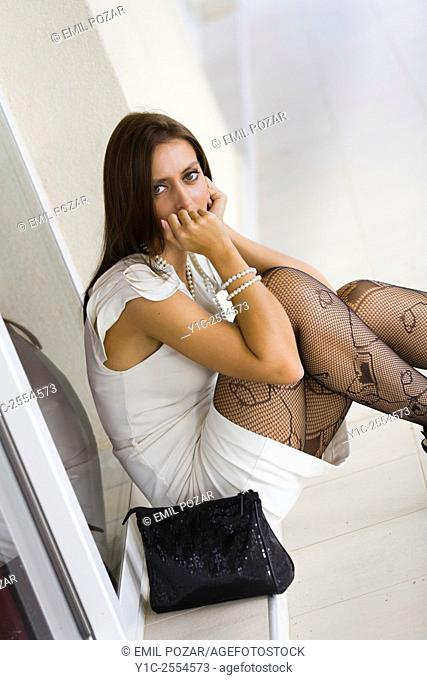 Stock Photo - Young woman concerned in White dress and fishnets