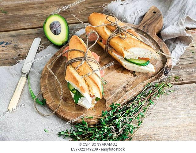 Salmon, avocado and thyme sandwiches in baguette tied up with decoration rope on a rustic wooden board over rough wood background