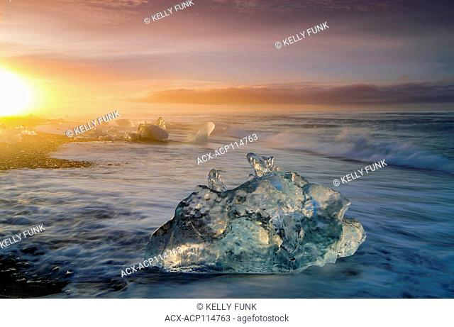 Pieces of Glacier from Jökulsárlón, a glacial lagoon, bordering Vatnajökull National Park in southeastern Iceland lay on the black sands of the Atlantic at...