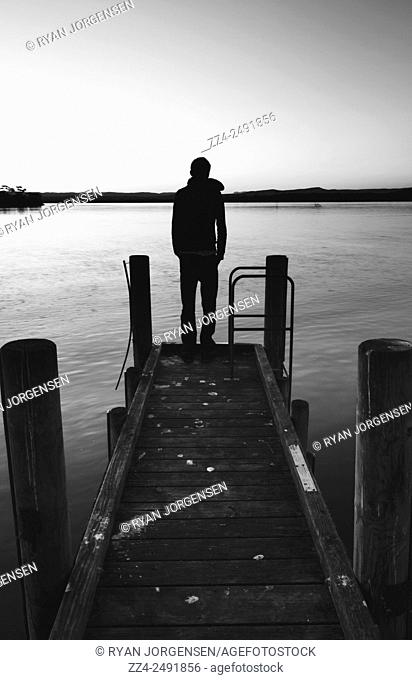 Black and white photograph of a man in early 20s enjoying a spring sunset when silhouetted from a small old pier promenade. End of grey days