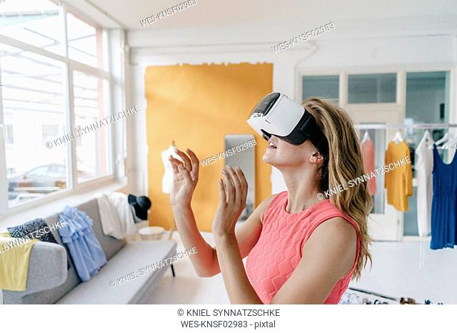 Young woman in fashion studio wearing VR glasses