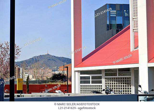 Red building, mountain, blue sky. Plaça Europa, Plaza Europa, District VII, Gran Via, Hospitalet de Llobregat, Barcelona province, Catalonia, Spain