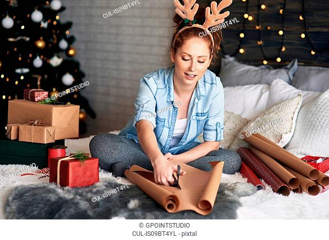 Woman wrapping Christmas presents on bed