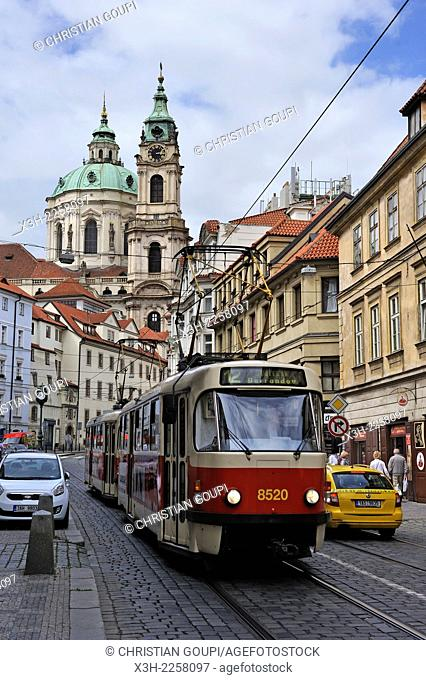 tramway in a street of Lesser Town Mala Strana district with the Church of St Nicholas in the background, Prague, Czech Republic, Europe