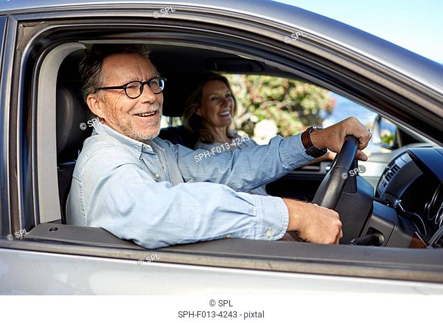 MODEL RELEASED. Senior man in car, smiling