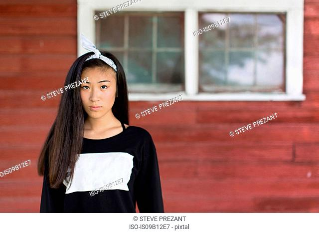 Portrait of teenage girl with long black hair and hair ribbon in porch
