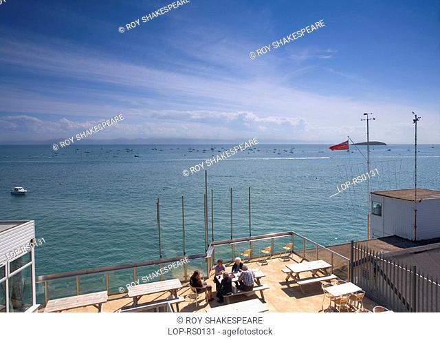 A group of people sitting at a table outside a cafe enjoying the view out to sea at Abersoch. As far back as the 19th century Abersoch was popular with...