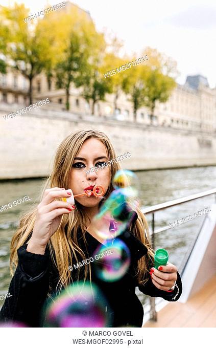 Paris, France, portrait of woman blowing soap bubbles