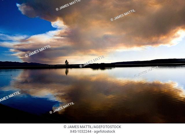 The sun reflects on Yellowstone Lake behind clouds of smoke from a forest fire