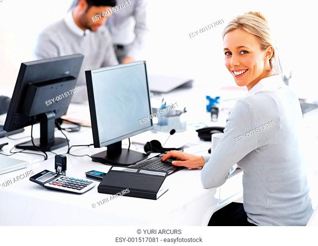 Portrait of smiling business woman at desk using computer with colleagues in background