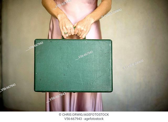 A woman in a pink slip holds a vintage suitcase