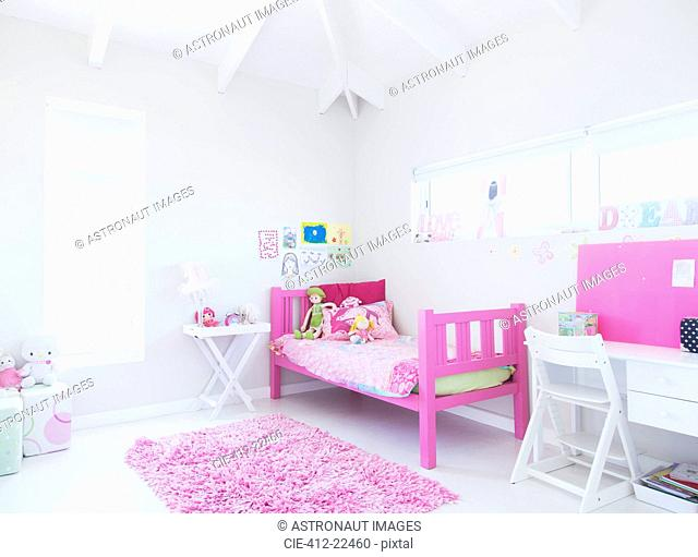 Girl's bedroom with pink bed, rug and toys