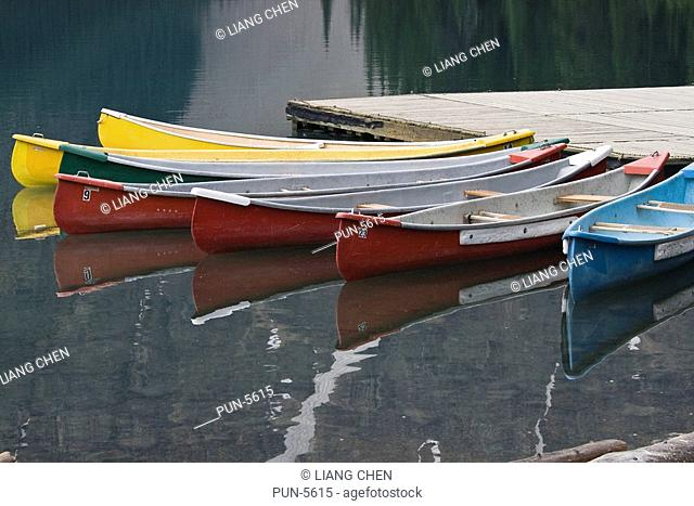 Docked boats with their reflections on Moraine lake in the early morning