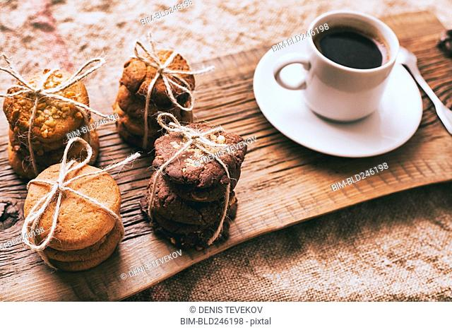 Coffee and bundles of cookies on wooden tray