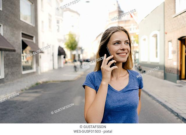Netherlands, Maastricht, smiling young woman on cell phone in the city