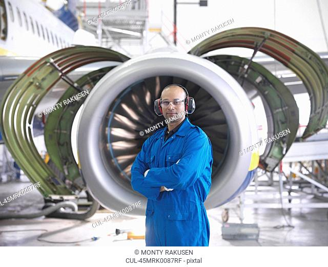 Worker standing by airplane engine
