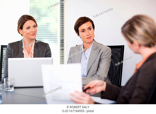 Smiling businesswomen with laptop meeting in conference room
