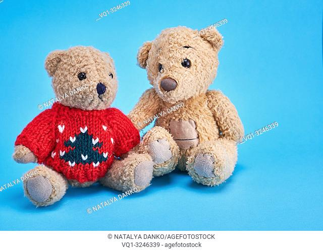 two teddy bears are sitting side by side on a blue background