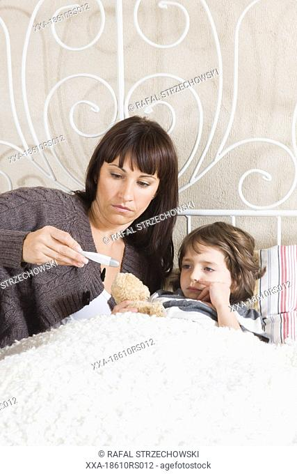 mother measuring child body temperature