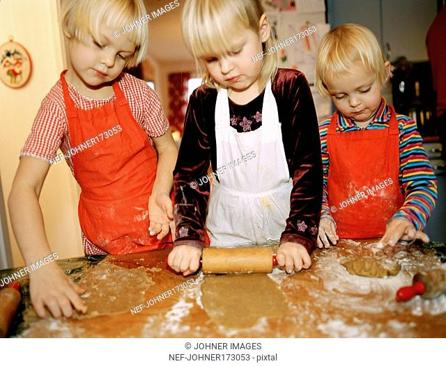 Children baking gingerbread cookies